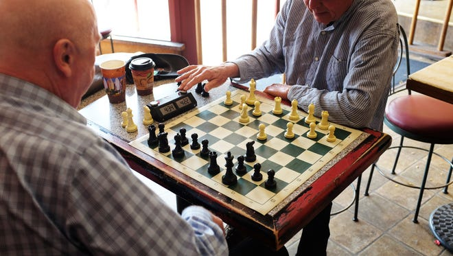"""Gary Jones, right, completes a move in a """"blitz chess"""" match at the Cherry Bean Coffehouse in Salinas."""