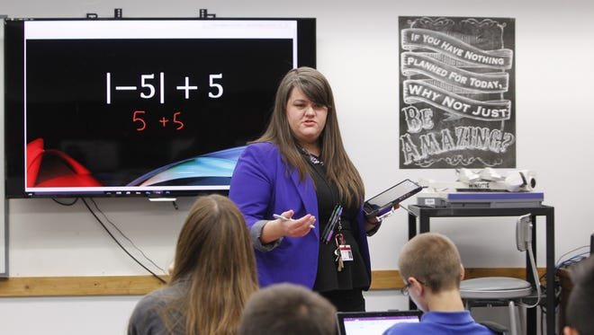 Summer Winrotte walks about her classroom checking students' work on their Microsoft Surface Pros while controlling the white board's content.