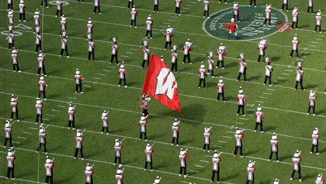 Bucky Badger runs between member of the Wisconsin's marching band before the game.