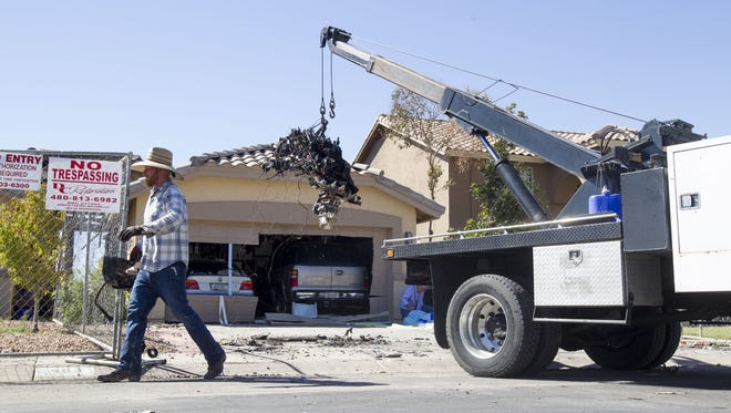 Emergency personnel pull airplane wreckage from a house at the 400 block of East Baylor Lane in Gilbert on Sunday, Sept. 18, 2016. A small airplane crashed into the home late Saturday night.