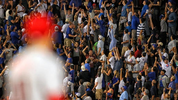 Chicago Cubs fans cheer after shortstop Addison Russell's (27) solo home run during the seventh inning of the game, while Cincinnati Reds first baseman Joey Votto (19) looks on at Wrigley Field.