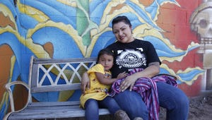 Chef Maria Parra Cano takes a break from cooking and holds her 3-year-old daughter Yalehua. Parra Cano was preparing beans, squash and deer and bison meat for the Indigenous Peoples Day celebration in Phoenix on Oct. 10, 2016.