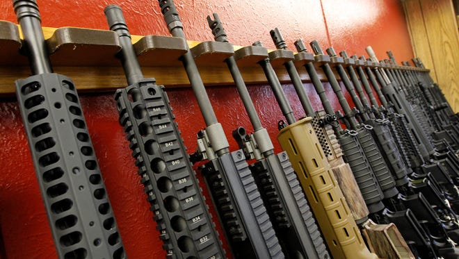 A row of different AR-15 rifles are displayed for sale July 20, 2012 at the Firing-Line indoor range and gun shop in Aurora, Colo.
