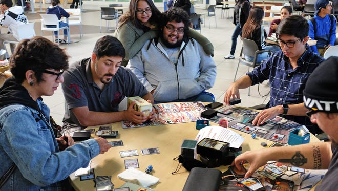 From left, Moses Chavez, Jose Marquez, Lisa Walton, Miguel Sanchez, Omar Cervantes and Dakota Sandoval play Magic:The Gathering at Hartnell's Student Center in Salinas.