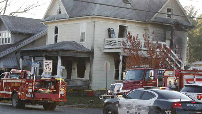 Crews investigate an early Monday fire in Flora that killed four children and injured two police officers.