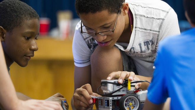 Gerald Bowers (right), 13, tinkers with a robot as Sonny Lavender, 13, looks on at Hartford Sylvia Encinas Elementary School in Chandler on Sept. 17, 2016. Season for Sharing helps with education programs for kids.