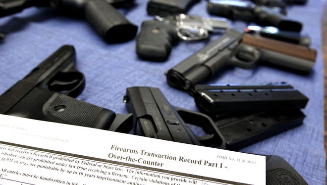 A federal firearms transaction record, which includes a background check, lays near a selection of guns at Ron's Pawn and Gun in Des Moines.