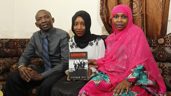 Zeynab Ali (center),18, sits with her father Osman Hassan and mother Isha Adan in their north side home in Milwaukee.
