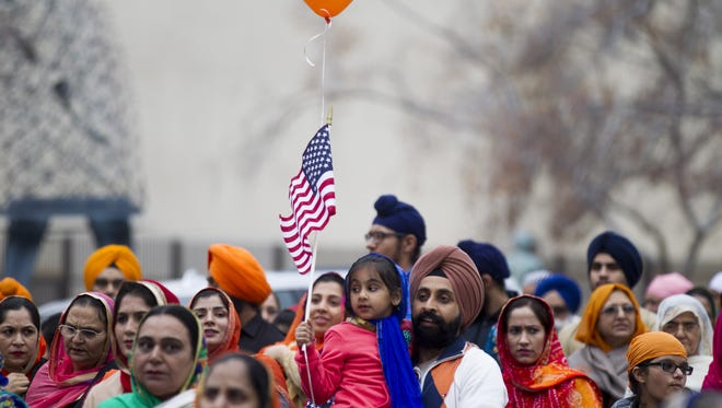 Pawitter Bhatia, right, carries his daughter Sehaj Bhatia in a parade during festivities for Sikh Awareness and Identity Day in downtown Phoenix on Sunday, Jan. 15, 2017.