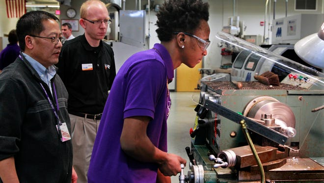 Desmond Glenn, 18, (right) works on a manual lathe machine while carving out a chess piece in a welding class at Bradley Tech high school. Watching are machine tool instructor Nou Vang (left) and Jonathan Feld,  project manager from MATC (back center).