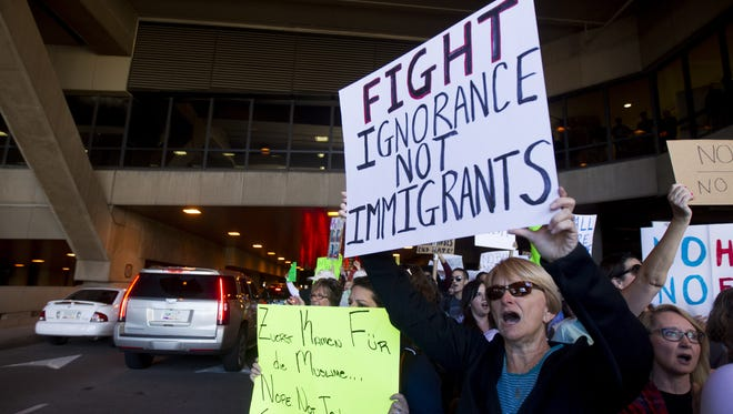 "Terry Gunn, 63, holds a sign that reads ""Fight ignorance not immigrants"" during a protest at Sky Harbor International Airport in Phoenix on Sunday, Jan. 29, 2017. Protests have broken out at airports across the country in response to President Donald Trump's executive order, signed Friday, placing a temporary ban on entrance to the U.S. by people from seven majority-Muslim countries."