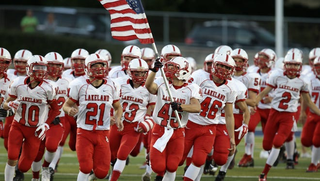 Darren Gould of Lakeland carries the American Flag as he leads the team onto the field during high school football action Lakeland Regional versus Paramus in 2014. Lakeland is hoping to replace the sports field with artificial turf by the beginning of the next school year.