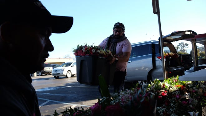 Arturo Moreno, owner of Flores Maryfer on E. Alisal St., unloads his van full of floral arrangements for Valentine's Day in Salinas.
