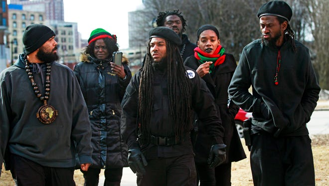 Alli Muhammad (center),  a leader of the Revolutionary Black Panther Party, arrives with others from the group to speak at a  news conference Wednesday at Red Arrow Park.
