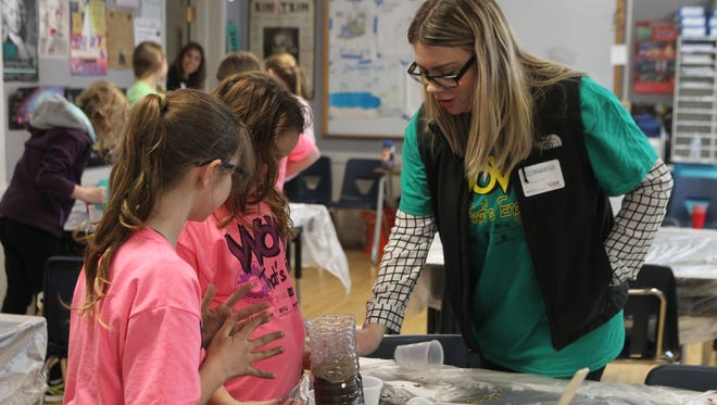 Jacqueline Todak, right, assists two girls during a soil-sampling workshop Saturday at the Wow! That's Engineering event.