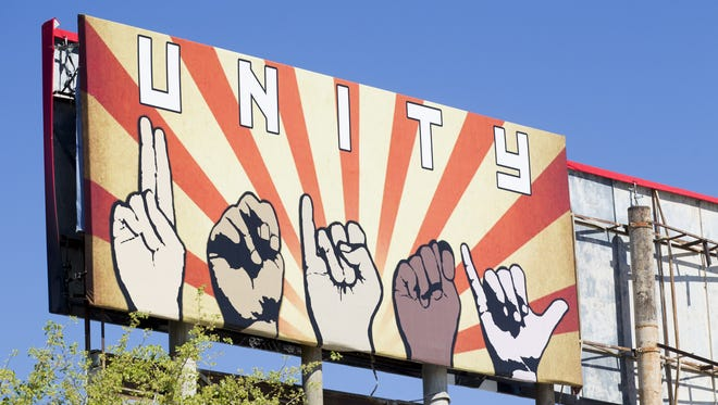 "A billboard depicting the word ""unity"" spelled out in sign language is displayed at the corner of Grand Avenue and Taylor Street in Phoenix on Sunday, March 19, 2017. Artist Karen Fiorito created the piece on commission from La Melgosa, a Phoenix art gallery, and has received death threats for the work."