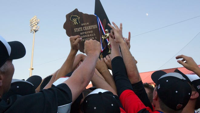 Burlington players hold the WIAA Division 1 state championship baseball trophy after defeating Arrowhead on June 16, 2016, in Grand Chute, Wis.