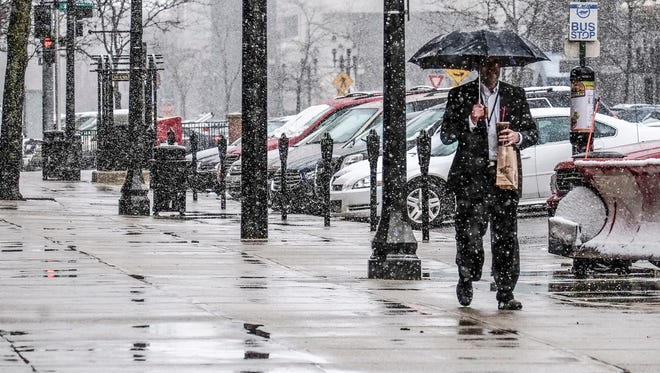 Wet snow comes down pretty hard during the lunch hour, bringing out the umbrellas Thursday, April 6, 2017.
