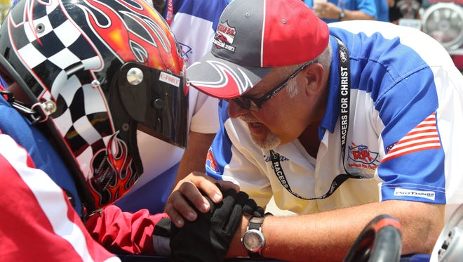 Chaplain Mike Griffith, with Team Racers for Christ, prays with drag racers as they line up to have their boats lowered into the water at the starting line during a previous Showdown in San Angelo.