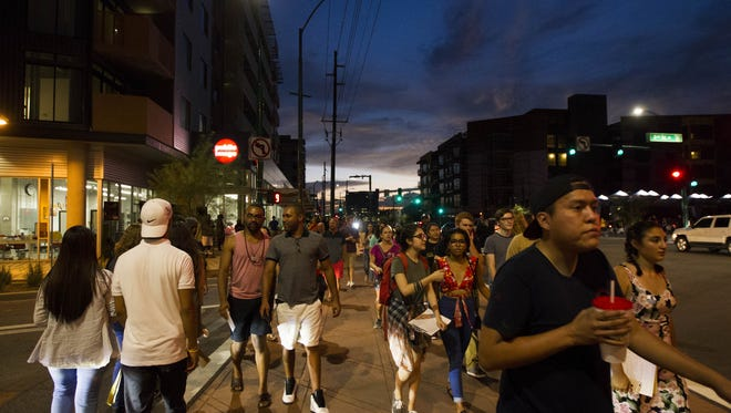 Pedestrians walk along Roosevelt Street during First Friday on Roosevelt Row on Aug. 5, 2016.