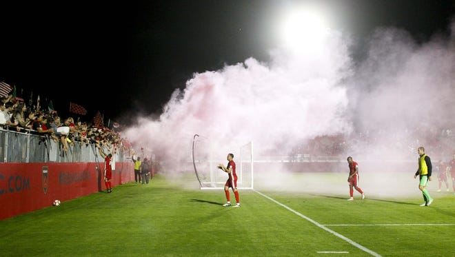 A cloud from a smoke bomb billows over the field after a game between Phoenix Rising FC and Toronto FC II at Phoenix Rising Soccer Complex in Scottsdale on Saturday, March 25, 2017.