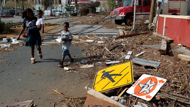 A woman with her two children walk past debris left by Hurricane Irma in Charlotte Amalie, St. Thomas, U.S. Virgin Islands, on Sept. 10, 2017.
