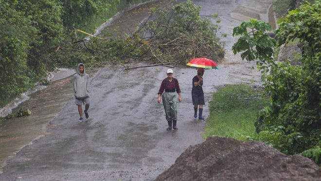 Neighbors walk under the rain past a washed out road in Alajuelita on the outskirts of San Jose, Costa Rica, Thursday, Oct. 5, 2017. Tropical Storm Nate formed off the coast of Nicaragua on Thursday and was being blamed for at least 17 deaths in Central America as it spun north toward a potential landfall on the U.S. Gulf Coast as a hurricane over the weekend. (AP Photo/Moises Castillo) ORG XMIT: XMC104
