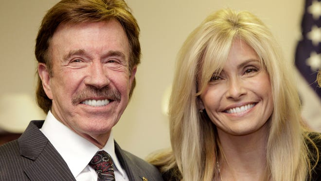 In this Dec. 2, 2010 file photo, actor Chuck Norris, left, and his wife Gena pose for a photo following a ceremony in Garland, Texas. Norris is taking on medical device manufacturers in a lawsuit alleging a chemical used in MRI imaging scans poisoned his wife.