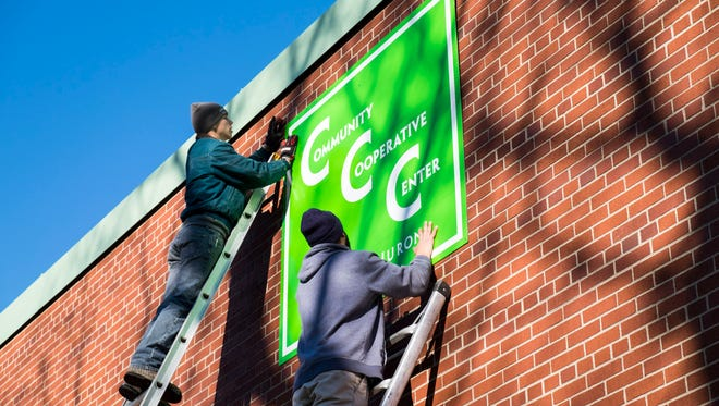 Brandon Lawrence, left, and Scott Berry, employees of Aarow Sign, hang a sign on the outside of First Congregational Church for the Center of Port Huron.