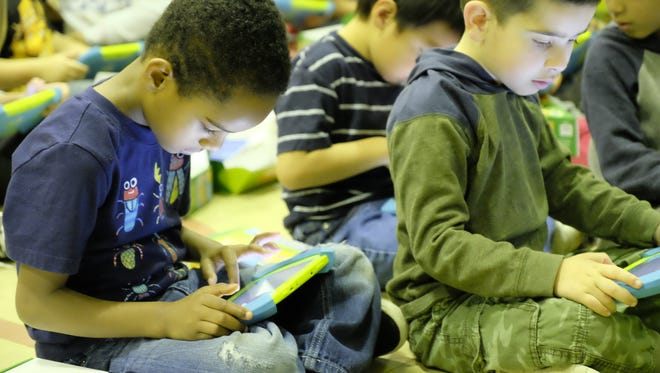 Paris Street, left, and Mateo Farhat, right, look at the new PBS Playtime Pads delivered to Kendon Elementary Monday, Nov. 13, 2017. The viewing habits of kindergartners will be analyzed by researcher at Michigan State University.