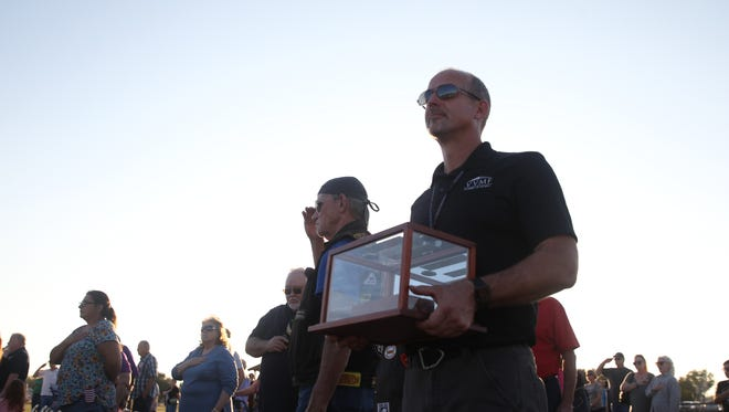 """Patrick O'Neill, site manager for the Wall That Heal, holds a brick from the """"Hanoi Hilton"""" during a ceremony Thursday at Fort Concho."""