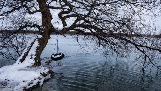 A tire swing coated with snow hangs off a tree over the St. Clair River in Marysville.