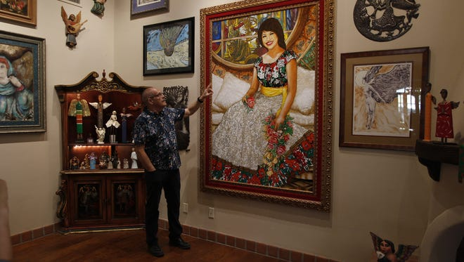 José Cardenas points to a painting of his beloved Virginia