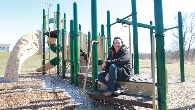 Hickory Trail Park will soon become Calder Park in honor of Calder Wills, a 12-year-old who died of cancer last year. In the above picture, Calder's mom, Brianna Wills, poses on a playground in the park.