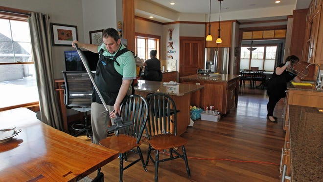 Spring cleaning means paying attention to every surface in your home, says Tim Denno of Tidy Tim's cleaning service, shown here at work in a home with Becky Boisvenue (by window) and Rachel Denno.