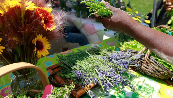 Alice, nws, adp, 19 of - Venice Williams, executive director for Alice's Garden, prepares to bag lavendar for a customer on Thursday, July 9, 2015 at the Schulitz Park Farmer's Market on 2nd street in Milwaukee. Angela Peterson/apeterson@journalsentinel.com