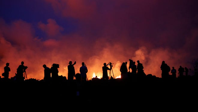 Residents and members of the media are silhouetted as active lava fissures near what is now the end of Leilani Street continue to spew forth lava at Leilani Estates near Pahoa, Hawaii on May 24, 2018.