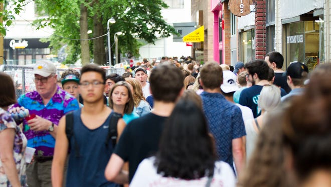 Community members pass along the pedestrian mall during Iowa CityÕs Downtown Block Party on Saturday, June 23, 2018. The event featured a volleyball tournament, mini golf, a silent disco, live music, and open container alcohol, marking the second year of the annual event.