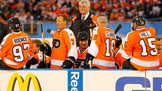 Members of the Philadelphia Flyers Alumni team, from the left, Bill Barber, Eric Lindros, Bob Clarke and coach Pat Quinn (standing) on the bench during the Winter Classic Alumni hockey game with the New York Rangers Alumni team, Saturday, Dec. 31, 2011 in Philadelphia. (AP Photo/Tom Mihalek)