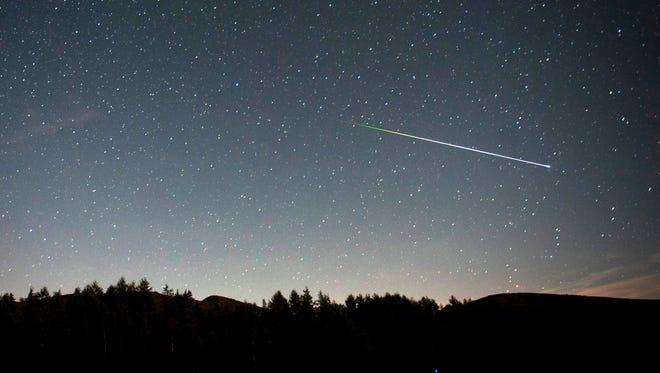 A meteorite of the swarm of meteorites Perseida burns up in the atmosphere above San Miguel de Aguayo village, in Cantabria, northwest Spain.