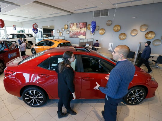 Sales person Trevor Meney explains car features to Julia Ragaglia of Gates at the Toyota location of the Dorschel Automotive Group.