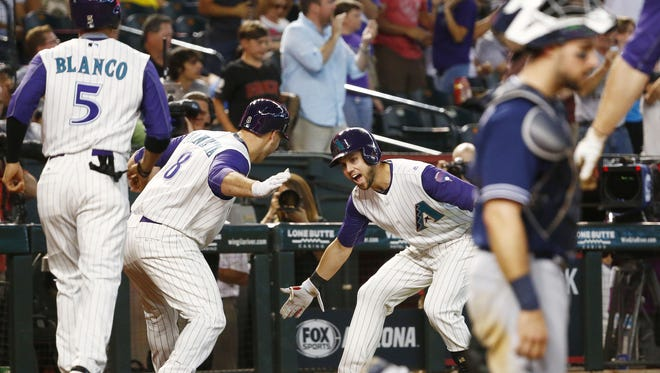 Arizona Diamondbacks Chris Iannetta low-fives Chris Owings after hitting a 2-run homerun, Gregor Blanco scored against the San Diego Padres in the 5th inning on Thursday, June 8, 2017 at Chase Field in Phoenix, Ariz.