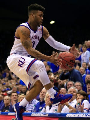 Kansas guard Frank Mason III (0) goes over the writers table after a loose ball during the first half of an NCAA college basketball game against Baylor in Lawrence, Kan.