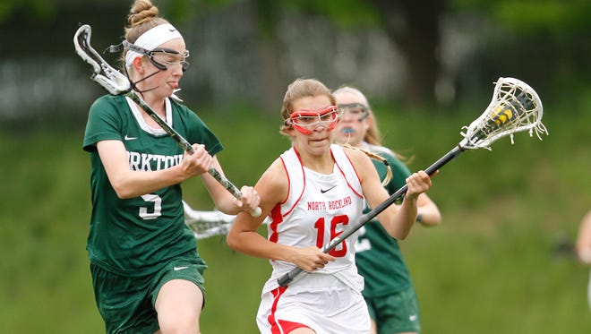 North Rockland's Ashley Morales (16) works the ball against Yorktown's Ciara Frawley (5) during a girls lacrosse game at North Rockland High School in Thiells on Tuesday, May 10, 2016.
