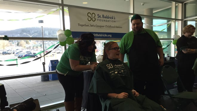 Binghamton University assistant softball coach Meredith Allen gets her hair cut as part of the athletic department's St. Baldrick's Foundation fundraiser at the Events Center on Tuesday.