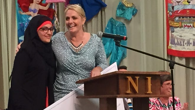 Siegel Middle School student Rawan Haj-Hussein embraces Northfield Elementary School teacher Tammy Sutton after both were honored at an assembly on Thursday.