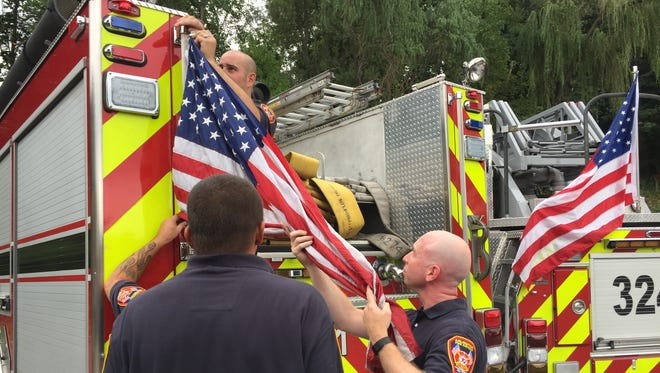 Arlington firefighters remove an American flag from a fire truck Tuesday after direction from the board
