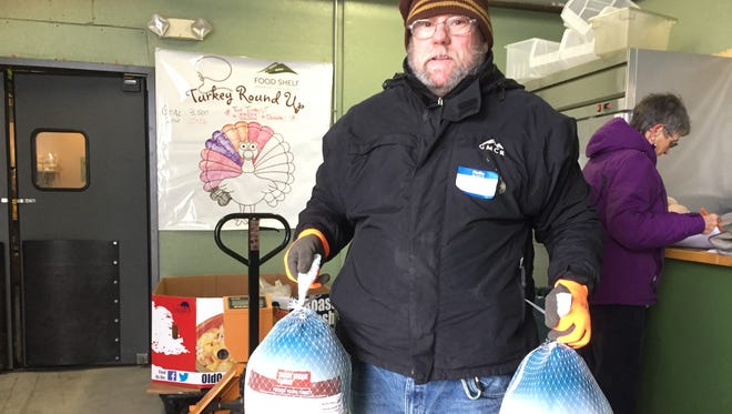 Wendell Russell of Hinesburg, a volunteer at Chittenden Emergency Food Shelf, hoists two donated turkeys in 2016. Behind him, Barb Sirvis of South Burlington, also a volunteer, updates a total of donated birds. Photographed Nov. 21, 2016.