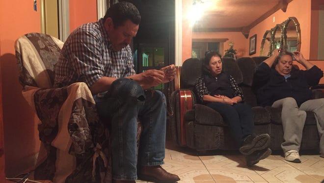 Geronimo Betancourt of Indio prays the rosary while Magda Sanchez and Nora Barrera pray silently.