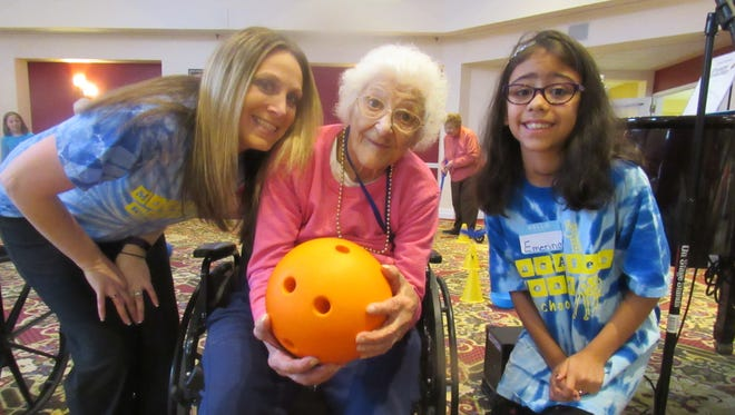 Spring Hills Somerset Assisted Living resident Mary Mupo (101 years old) poses with MacAfee Road School student Emerina Hawkins (right) and her physical education teacher Alyson Samarel.